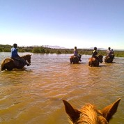 Crossing the river on horseback.